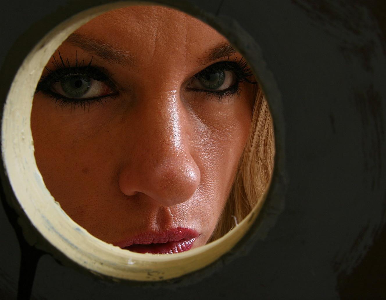Парень сует член в ротик длинноногой блондинистой девчушке через дырочку в стене