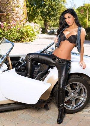 Опытная модель показывает свои нежные сиськи стоя возле машины