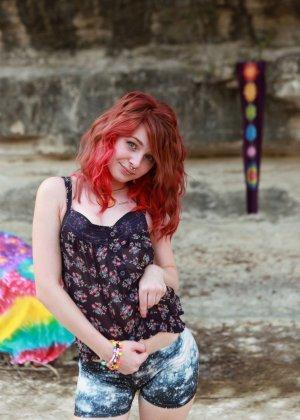 Девушка с яркими волосами раздевается на природе, демонстрируя свое хорошее тело всем желающим