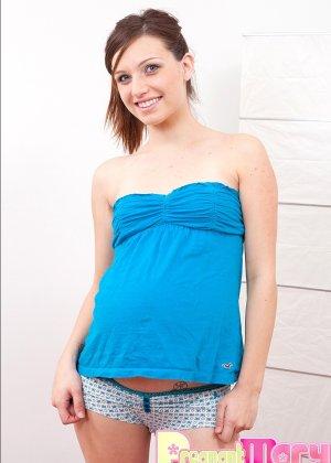 Беременная девушка раздевается и ласкает свое тело руками, а затем включает вибратор и подносит к клитору