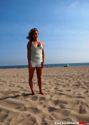 Сексуальная красотка в белом бикини показывает свою красоту на пляже, демонстрируя лучшие части тела