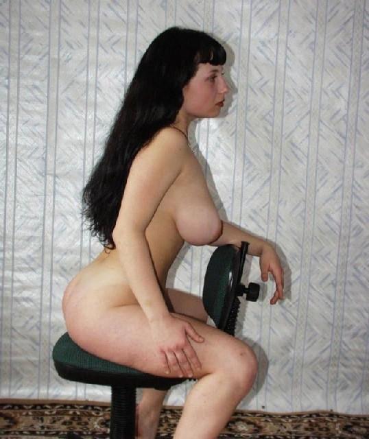 Фигуристая брюнетка с большой грудью позирует у себя дома