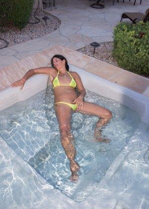 Женщина с большим клитором и в желтом купальнике расслабляется в ванной