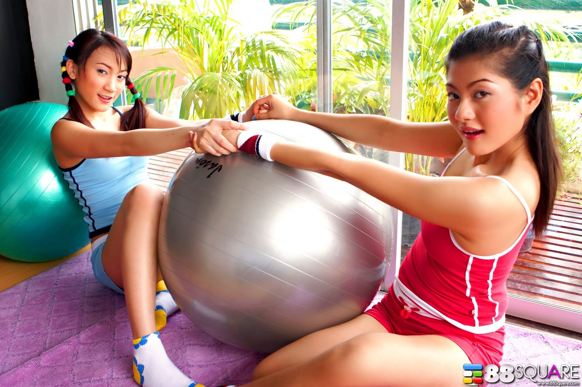 Две азиатки лесбиянки с в зале с большими мячами трогают волосатые вагины друг друга и ласкают розовые щели пальцами