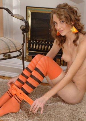 Девка в оранжевых гольфах показывает стриптиз у камина