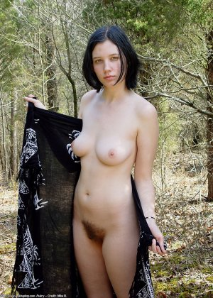 Голая брюнетка гуляет по лесу