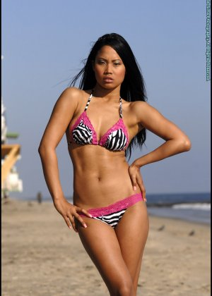 Азиатка снимает купальник на пляже