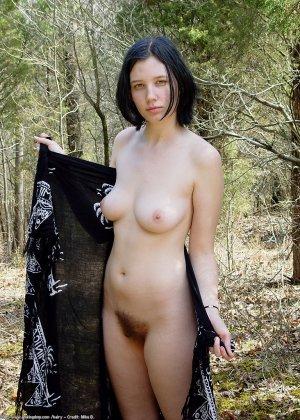 Голая брюнетка с волосатой вагиной позирует в лесу