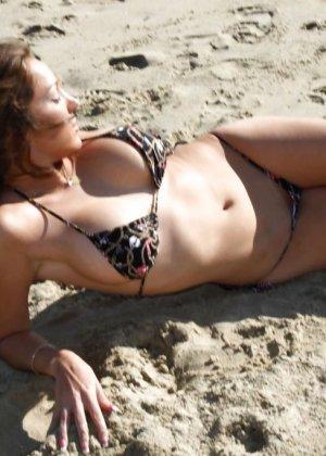 Женщина гуляла одна на пляже в купальнике