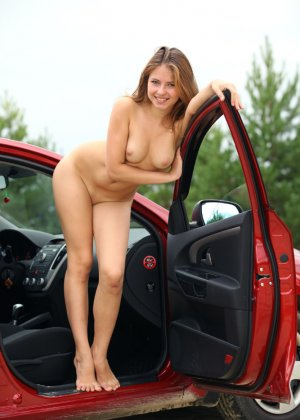Худая обнаженная девушка сексуально позирует в машине