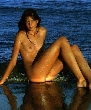Стройная брюнетка показывает свое идеальное тело на фоне морских волн – она выглядит умопомрачительно