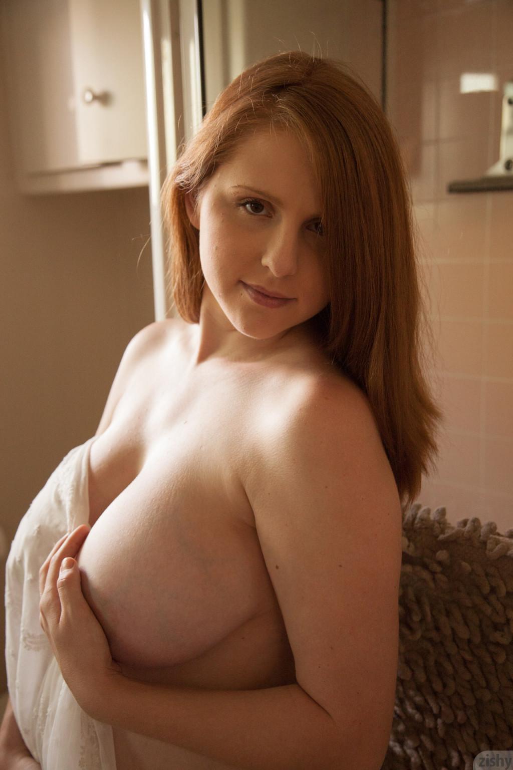 Рыжая беременная девушка приоткрывает ночную рубашку