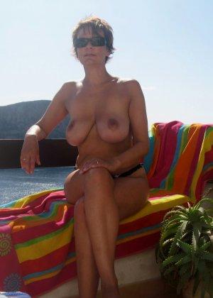 Пожилая Агата с большими сиськами загорает топлесс на пляже