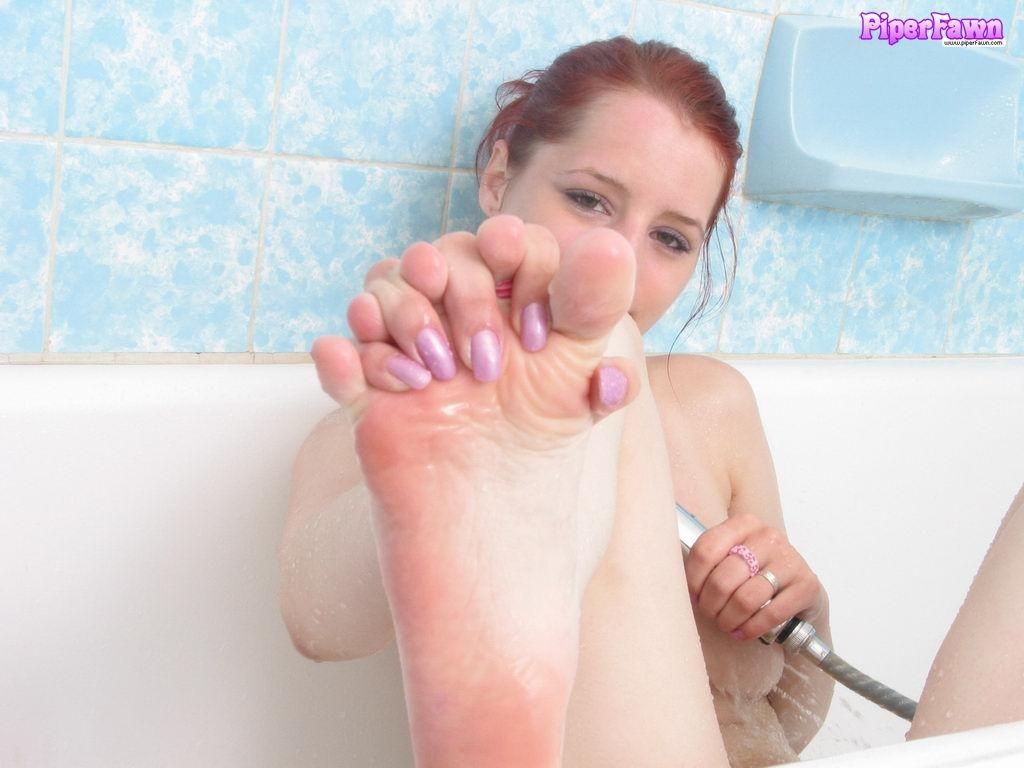 Рыжая девушка с классной попкой моет ножки в ванной