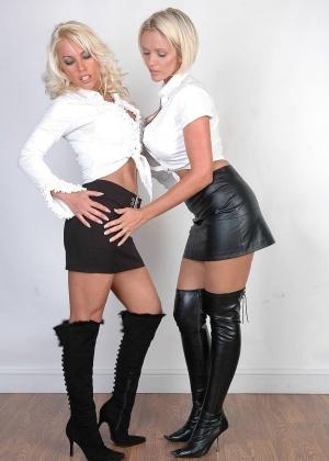 Две милфы блондинки в кожаных юбках и сапогах показывают сиськи